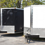 Three black and white transport trailers in a row.