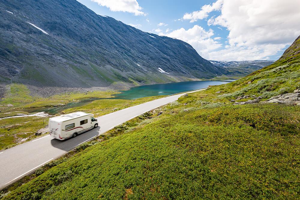 RV driving toward lake
