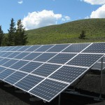 solar panels by a green hill