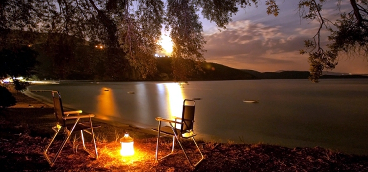 affordable ways to go camping, picture of a lantern in between two chairs on the shore of a lake, affordable camping