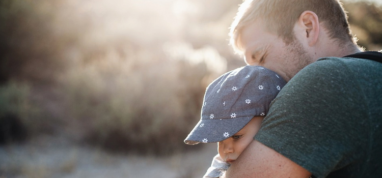 connect with nature while rving, 5 great ways to connect with nature while rving, picture of a dad holding his son while taking a hike in the woods