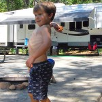 7 rving tips, picture of a kid having fun at a rv park with a fifth wheel in the background, rving with kids, rving with children
