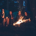 6 camping tips, picture of people gathered around a campfire with tents in the back while camping
