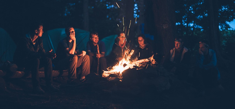 shower time while camping, 6 camping tips, picture of people gathered around a campfire with tents in the back while camping