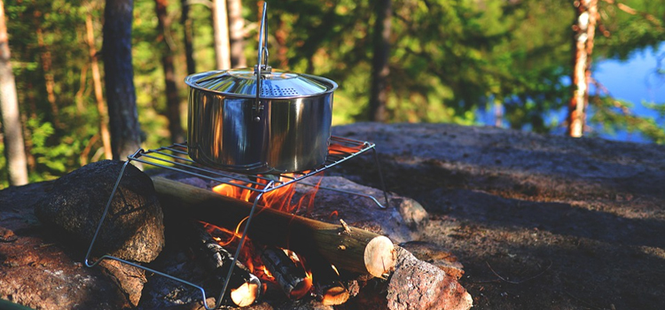 camping recipes, picture of a camp fire with a pot cooking on top of it