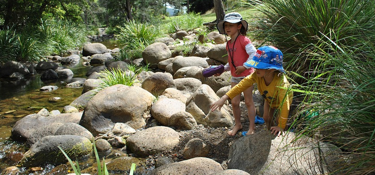 hiking with kids, picture of children taking a hike through a creek with big strones