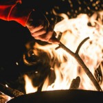 11 camping tips to consider when camping with your kids, picture of a womens hand adjusting a camp fire