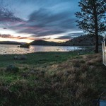 8 camping hacks that will make you an expert, picture of a travel trailer camped outside of a lake with a beautiful clouded sky and purple clouds