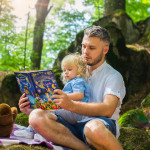 Father and daughter reading outside